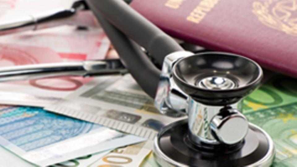 Ein Stethoskop liegt auf Geldscheinen. Im Hintergrund liegt ein Pass.