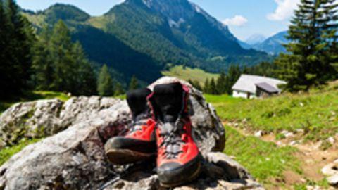 Wanderschuhe liegen auf einem Stein. Im Hintergrund sind Berglandschaften zu sehen.