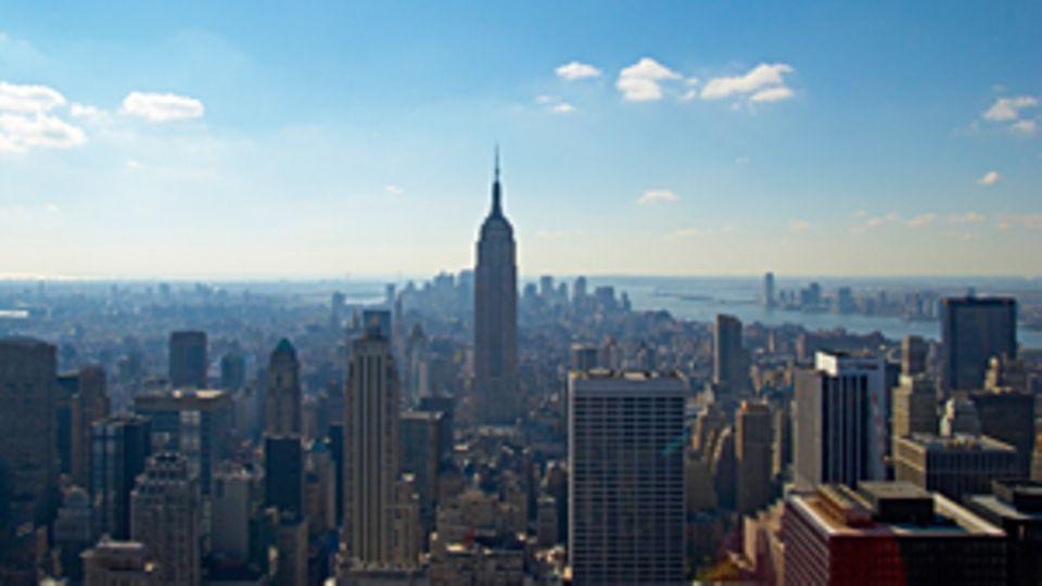 Ein Bild, über den Dächern von New York. Im Zentrum des Bildes ist das Empire State Building.