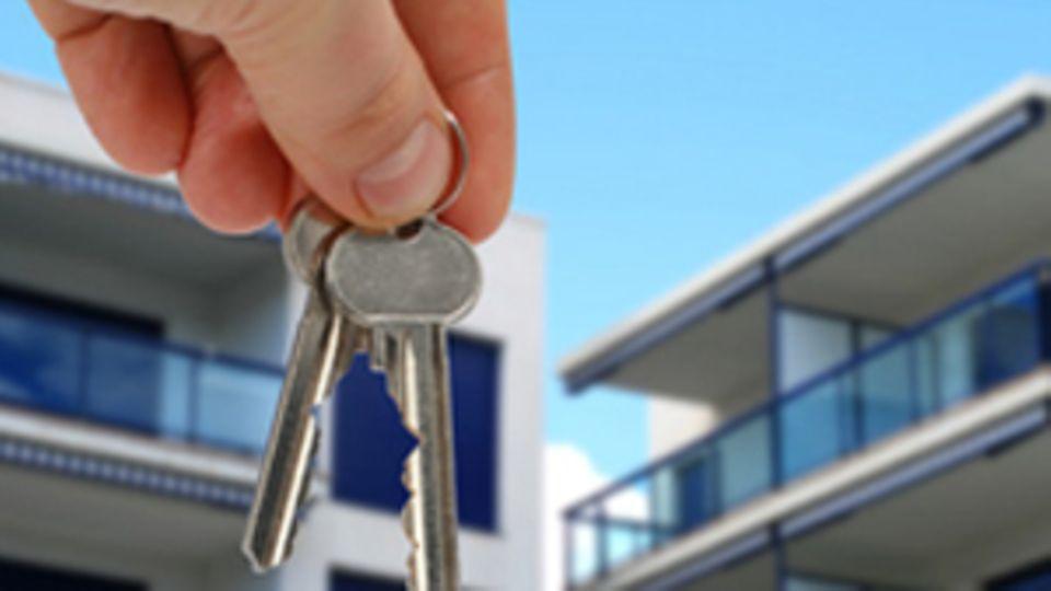 Jemand hält Schlüssel in der Hand. Im Hintergund sind Häuser zu sehen.