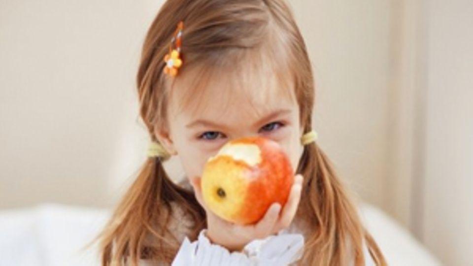 Eines kleines Mädchen hält sich einen angebissen Apfel vors Gesicht.