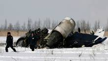 Security personnel walk at the site of a plane crash in Almaty airport December 26, 2007. A small German-owned private jet crashed during take-off from Almaty airport on Wednesday, killing its only passenger, Kazakhstan's Emergency Ministry said.  REUTERS/Pavel Mikheev (KAZAKHSTAN) - RTX50AJ