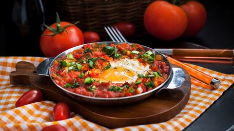 Shakshouka Dieses Gericht stammt aus dem arabischen Raum. Es handelt sich um pochierte Eier in einer Sauce aus Tomaten, Chilis, Zwiebeln und Kreuzkümmel.