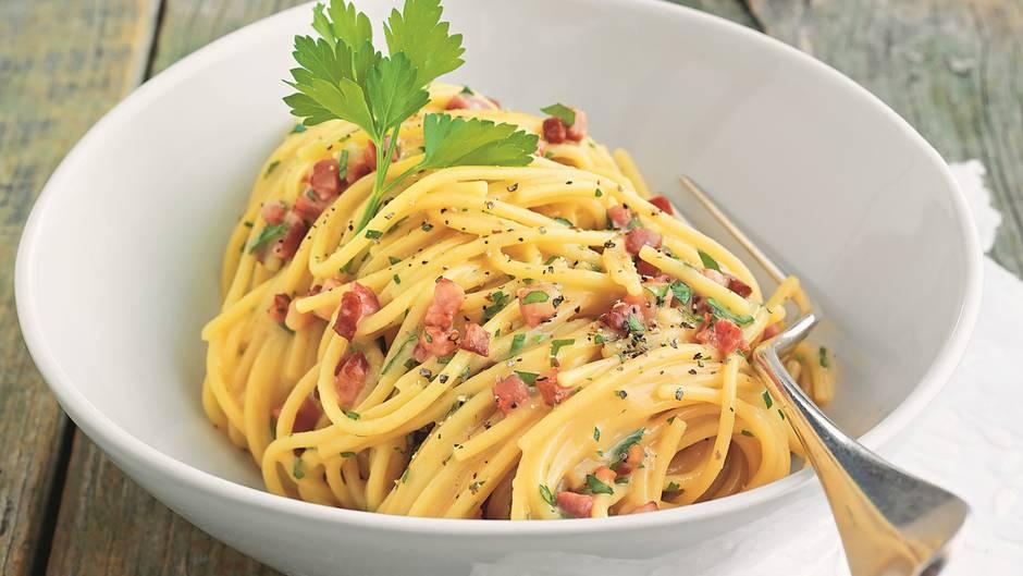 Ein Teller mit dampfender Pasta alla carbonara - ein Klassiker