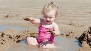 Ein Kind spielt im Sand - und zwar mit vollem Körpereinsatz