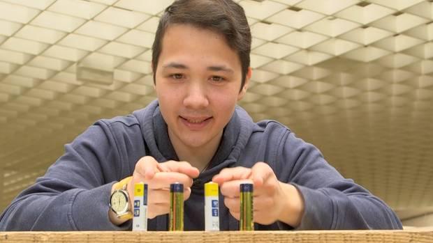 Vier Batterien stehen vor einem jungen Mann.