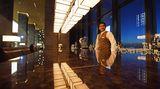 Im poliertem Marmortresen spiegelt sich die Bar, die sich wie das Restaurant hinter den Säulen der Lobby versteckt und durch die Ausrichtung nach Südwesten die Sonnenuntergänge einbezieht.