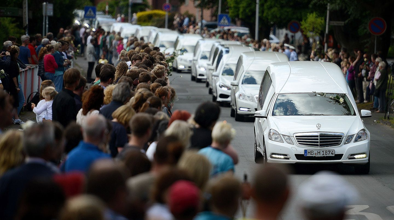 Ein Konvoi aus mehreren Leichenwagen fährt in Haltern an einer Menschenmenge vorbei