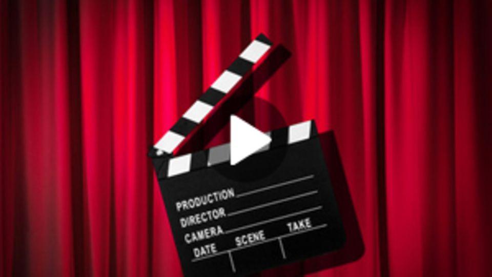 Eine Filmklappe vor einem roten Vorhang.