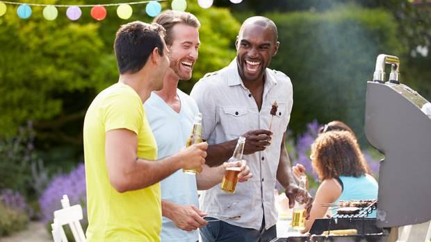 Männer stehen lachend um einen Grill herum