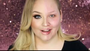 """Szene aus dem Video: """"Power of Make-up"""": Bloggerin Nikkie mit einer geschminkten Gesichtshälfte und einer ungeschminkten"""