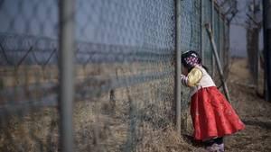 Südkoreanisches Mädchen blickt durch einen Grenzzaun