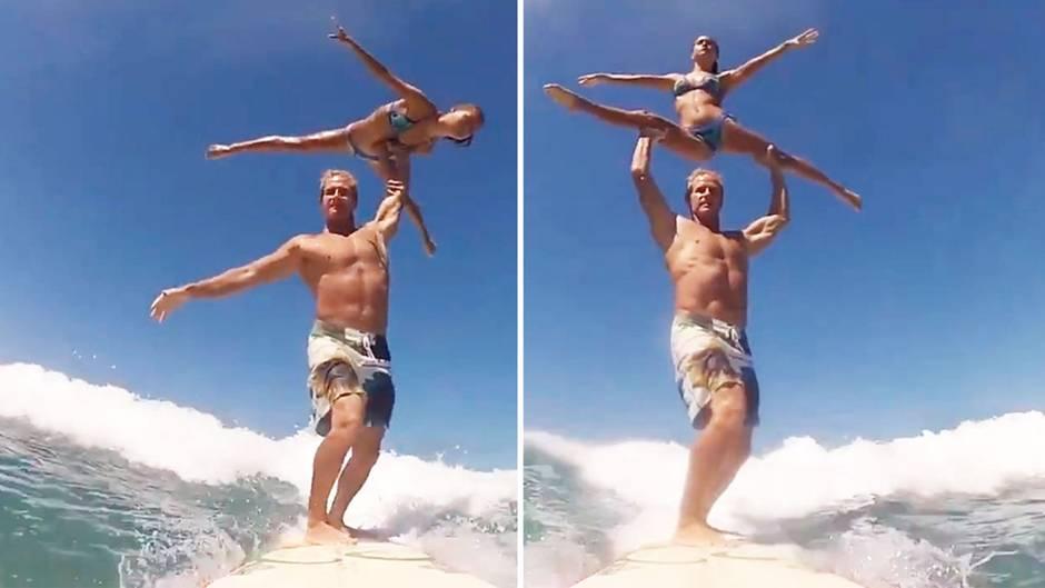 Surfer Pärchen macht akrobatische Übungen auf dem Brett