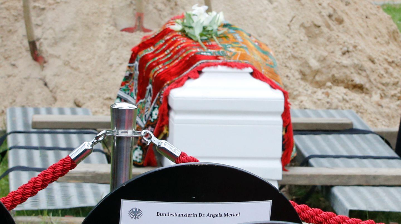 Ein Sarg mit den sterblichen Überresten eines im Mittelmeer ertrunkenen Flüchtlings steht auf Brettern über dem offenen Grab