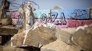 """Trümmer liegen vor einer Mauer mit einem """"Gaza""""-Grafitto"""