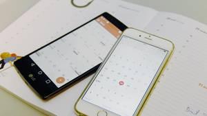 Ein iPhone und ein Android-Smartphone liegen mit geöffneter Kalender-App auf einem Papier-Planer