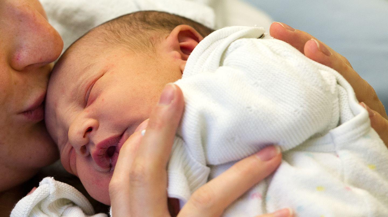 Ein Baby liegt mit geschlossenen Augen auf der Brust der Mutter. Sie hält es fest und küsst seinen Kopf.