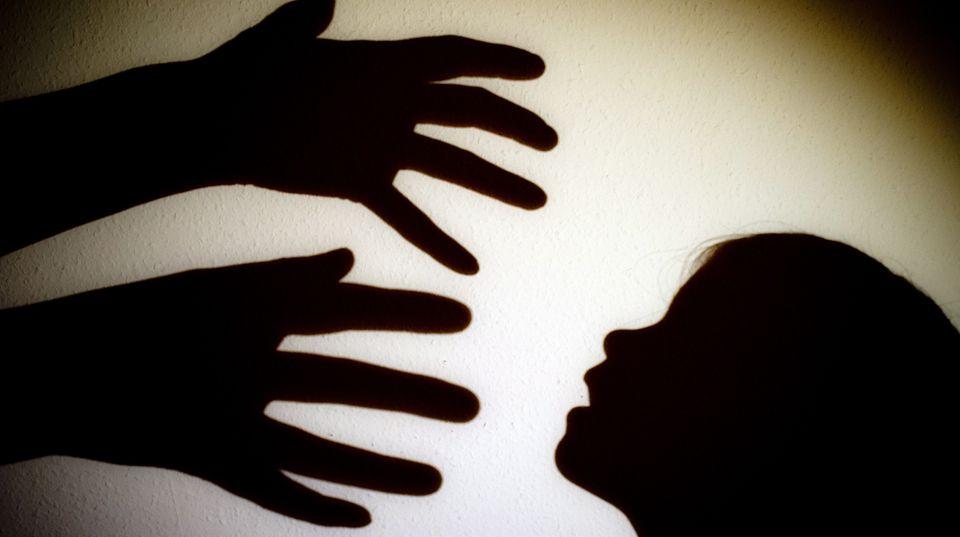 Schatten von Händen einer erwachsenen Person und dem Kopf eines Kindes an einer Wand eines Zimmers