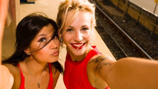 Zwei junge Frauen machen ein Selfie neben einem Bahngleis