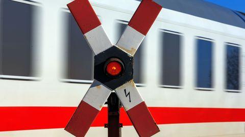 Ein rotes Warnsignal in einem Andreaskreuz leuchtet während ein Zug vorbei rast