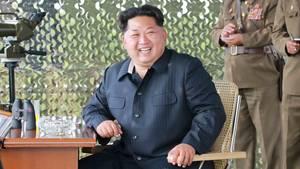 Kim Jong Un sitzt grinsend