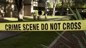 """Ein gelbes Polizei-Absperrband mit dem Schriftzug """"Crime Scene Do not cross"""" vor einer Gartenanlage bei Sonnenschein"""