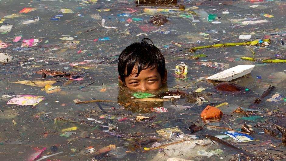 Ein Junge schwimmt in Manila in Wasser voller Müll