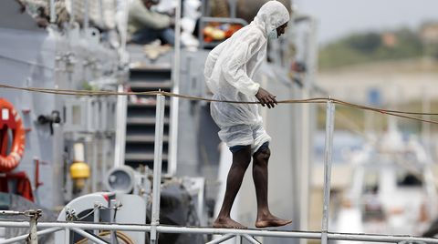 Ein geretteter Flüchtling läuft barfuss über die Stelling auf die Militärfregatte Fenice