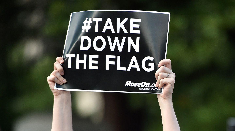 Zwei Händen halten ein Plakat mit der Aufschrift #take down the flag
