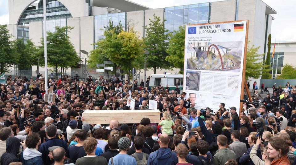 """Ein Holzsarg wird im Rahmen der Aktion """"Marsch der Entschlossenen"""" vom Zentrums für Politische Schönheitvor das Kanzleramt getragen. Im Hintergrund steht ein symbolisches Bauschild mit der Aufschrift """"Hier baut die Europäische Union - Friedhofsanlage - Den unbekannten Einwanderern"""""""