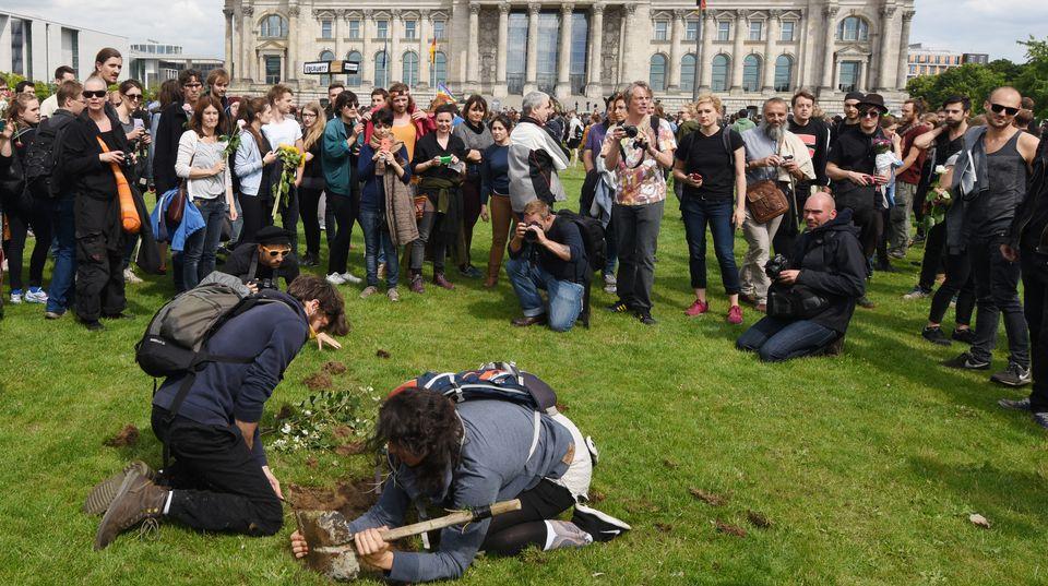 Die Toten kommen: In den Rasen vor dem Berliner Bundestag werden mit Schaufel und Händen symbolische Gräber für verstorbene Flüchtlinge gebuddelt