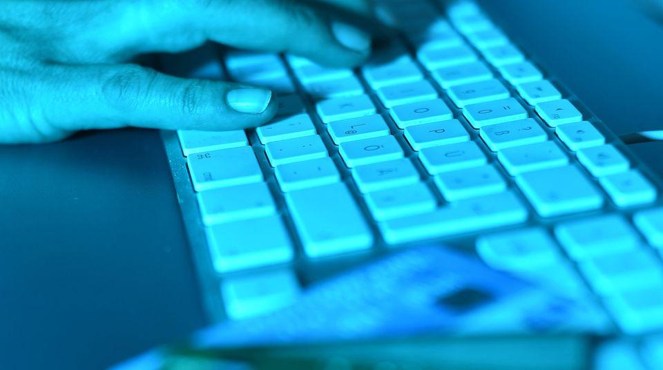 Die Abzocke bei Facebook durch Klon-Profile nimmt zu. Zu sehen ist eine Hand auf einer Tastatur, daneben Kredikarten