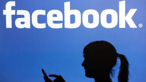 Vor dem Facebook-Logo ist der Schatten einer Frau zu sehen.