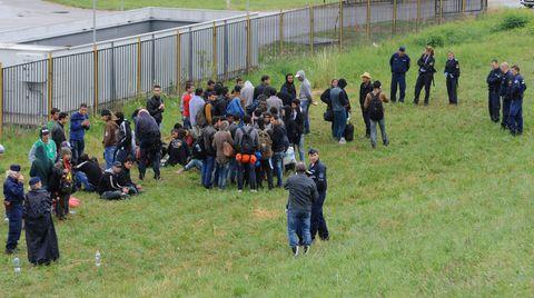 Ungarische Polizisten bewachen Flüchtlinge, die sie an der Grenze festgenommen haben