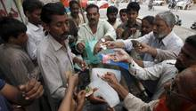 Menschen in der Hafenstadt Karachi stehen an, um Eisblöcke zu kaufen.