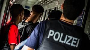 Ein Bundespolizist kontrollieren Reisende in einem Zug