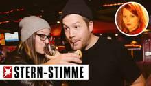 Zwei junge Menschen stehen in einer Bar und trinken Alkohol