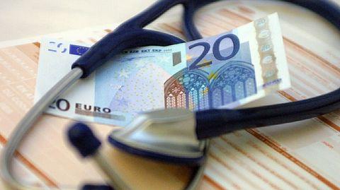 Ein Geldschein liegt neben einem Stethoskop