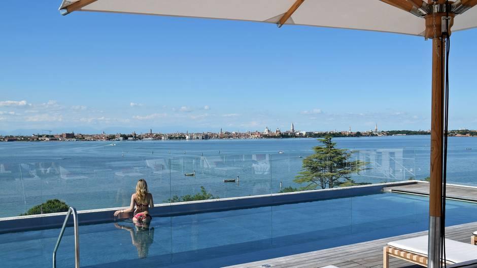 Rooftop-Pool mit Badegast und Blick auf die Lagune von Venedig