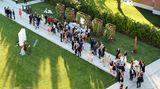Gäste mit Cocktailgläsern im Hotelgarten