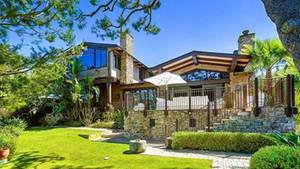 Das Haus ist umgeben von Palmen und Bäumen.