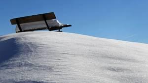 Eine Parkbank steht im Schnee. Während der Hitzewelle soll es in Köln schneien.