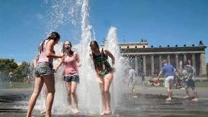 Hitze in Berlin: Kinder spielen vor dem Brandenburger Tor in einer Wasserfontäne