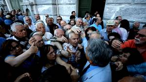 Ein Mitarbeiter der National Bank of Greece wird von Rentnern überwältigt, als er Wartenummern für die Geldschalter verteilt