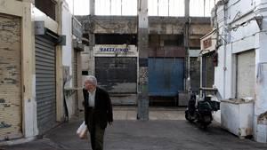 Griechischer Rentner vor verfallenen Häusern