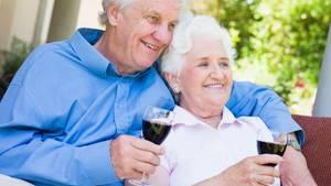 Ein altes Ehepaar sitzt auf der Terrasse und trinkt Rotwein