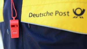 Ein Mitarbeiter der Deutschen Post demonstriert im Rahmen eines Warnstreiks der Gewerkschaft Verdi.