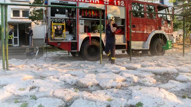 Feuerwehrmann steht in Hagelkörnern