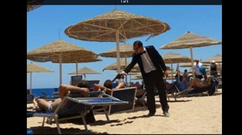 Hotelmitarbeiter im James-Bond-Look zielt mit einer Plastikpistole auf Urlauber