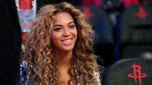 Sängerin Beyoncé  trägt ein tief ausgeschnittenes silbernes Kleid, ihr wallenden Locken ragen bis zu den Oberarmen